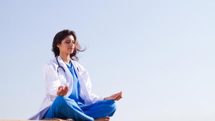 Person wearing lab coat sitting in meditation